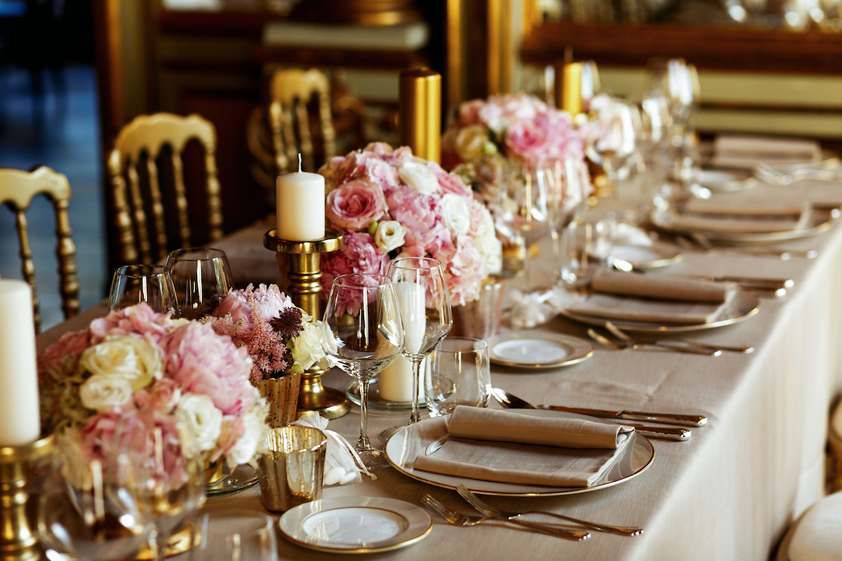 Long table served with porcelain crockery and shining cutlery served with pink flowers